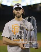San Francisco Giants pitcher Madison Bumgarner holds the World Series trophy after Game 7 of baseball's World Series Thursday, Oct. 30, 2014, in Kansas City, Mo. The Giants defeated the Kansas City Royals 3-2 to win the series. (AP Photo/Charlie Neibergall)