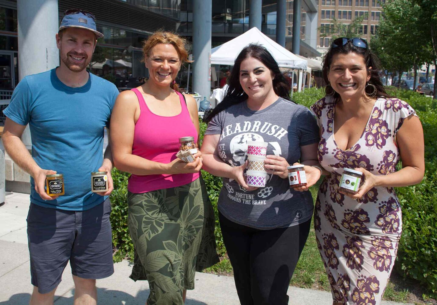Unique products, baking and produce are available at the outdoor Downtown Farmer's Market at Manitoba Hydro Place. The market, organized by Downtown Winnipeg BIZ, is open from 10 a.m. to 3 p.m. every Thursday during the summer months, until mid-September. It then reverts to a monthly event indoors. Pictured, from left, are Chris Kirouac (beeproject.ca), Rebecca Hadfield (zenbars.ca), Angela Filbert (whippedcosmetics.com) and Bessie Hatizitrifonos (bessiesbestfoods.com).  (John Johnston / Winnipeg Free Press)