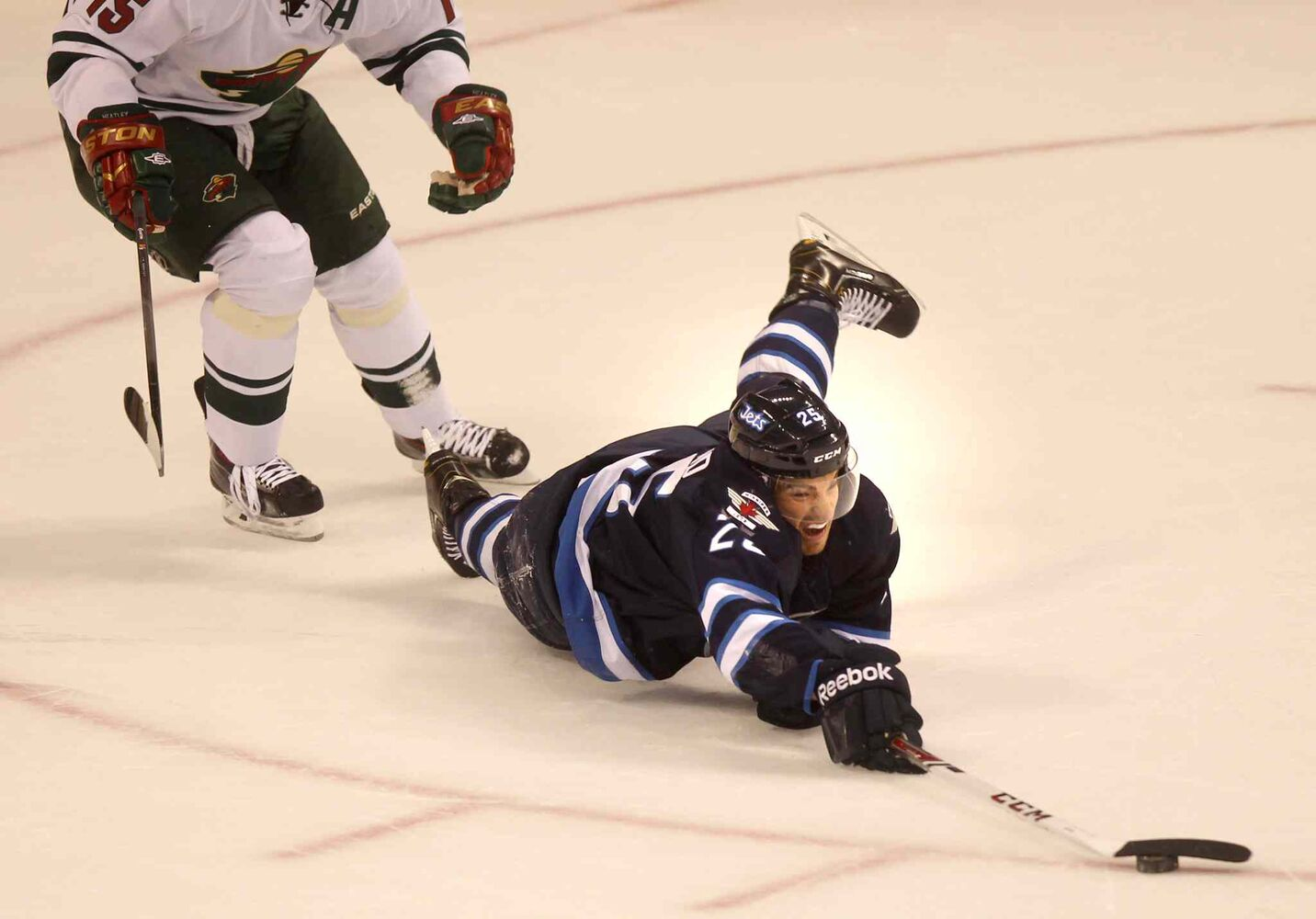 Zach Redmond dives for the puck after being tripped by Dany Heatley of the Minnesota Wild late in the first period.