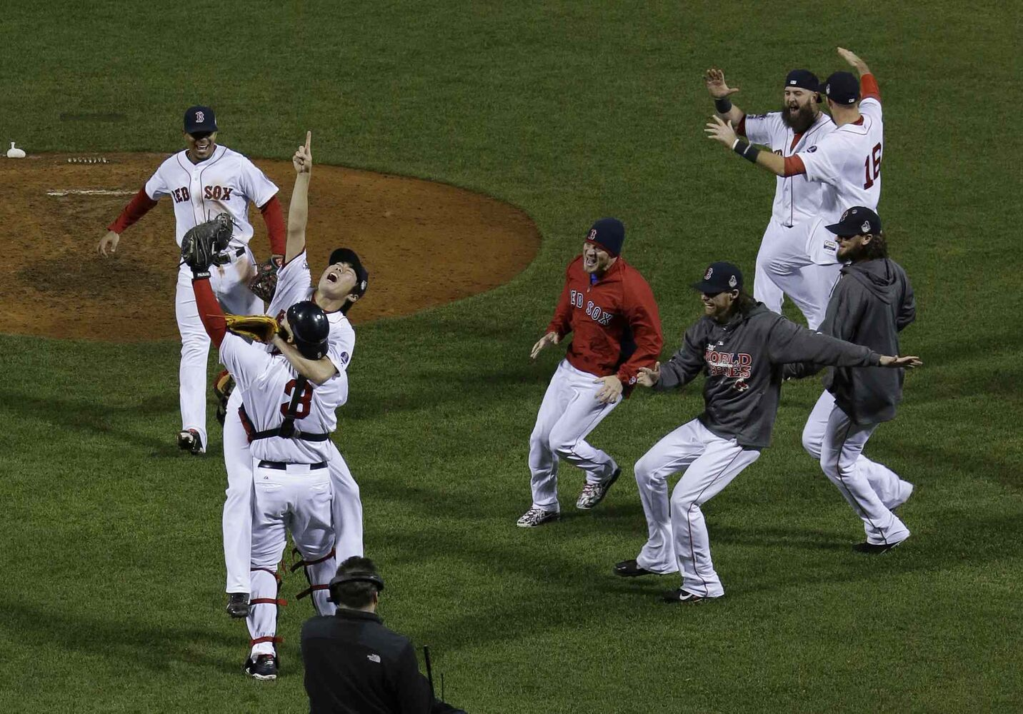 Boston Red Sox relief pitcher Koji Uehara (pointing skyward) jumps into David Ross's arms after defeating the St. Louis Cardinals in Game 6 of baseball's World Series Wednesday in Boston, Mass. The Red Sox won 6-1 to win the series. (Matt Slocum / The Associated Press)