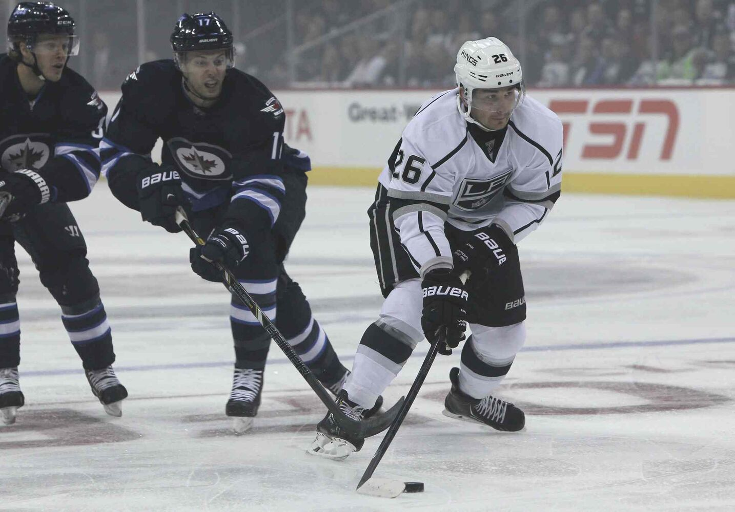 Winnipeg Jets' James Wright (17) tries to slow down Los Angeles Kings' Slava Voynov (26) in the first period. (MIKE DEAL / WINNIPEG FREE PRESS)