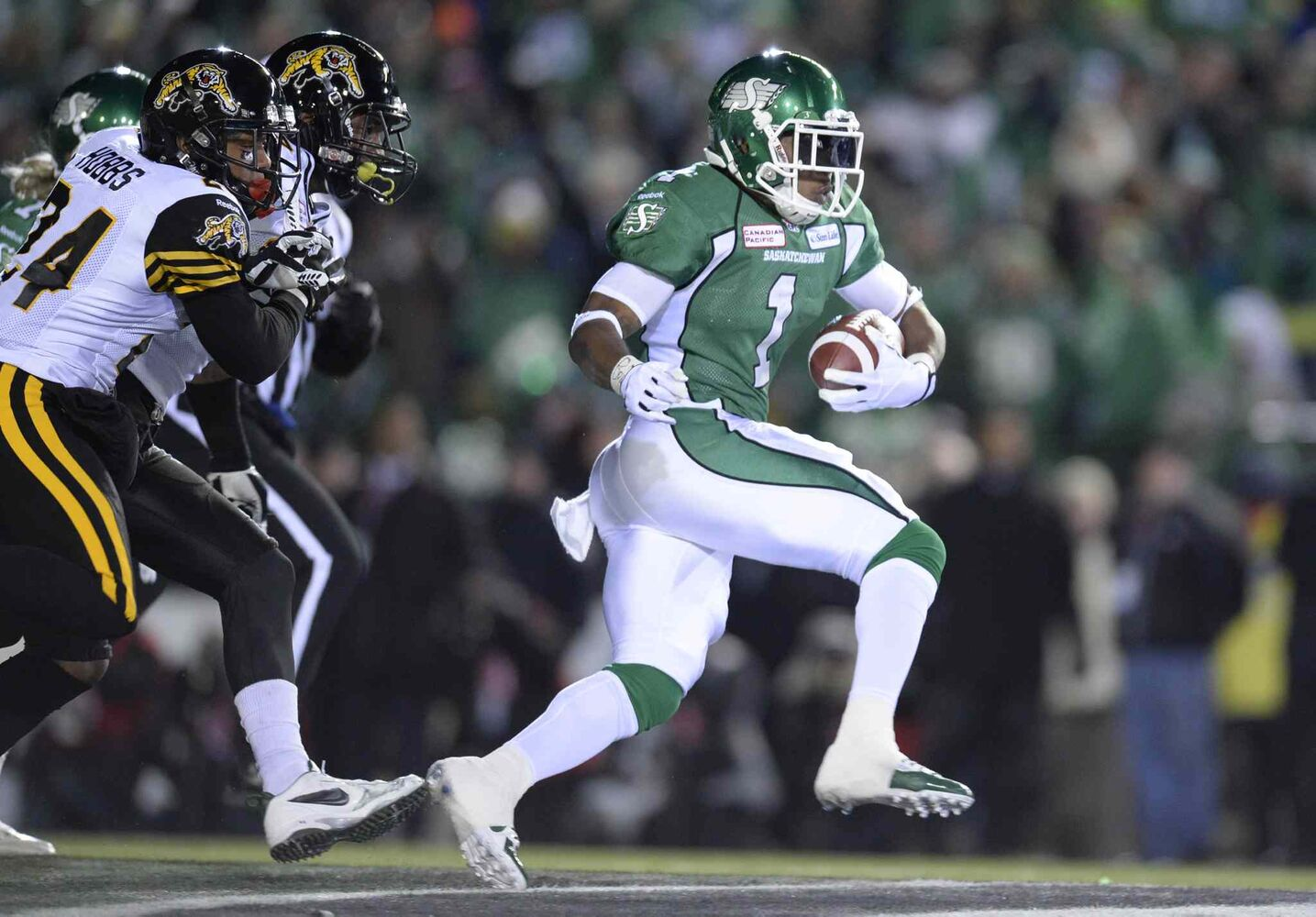 Saskatchewan Roughriders runningback Kory Sheets runs away from Hamilton Tiger-Cats players during the first quarter.