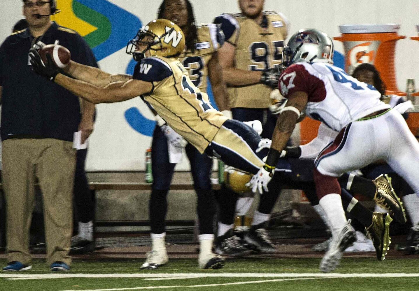 Winnipeg Blue Bombers' slotback Nick Moore catches a pass in front of Montreal Alouettes' defensive back Jamaan Webb during the third quarter of Friday's game. (Paul Chiasson / The Canadian Press)