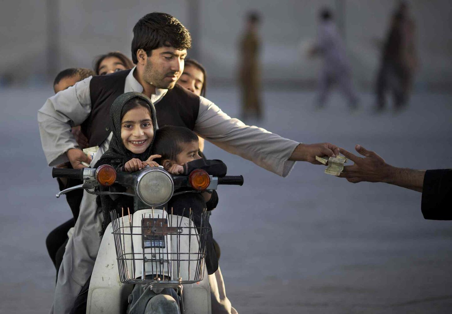 Nov. 1, 2013: An Afghan man with his five children on his motorbike pays money to enter a park in Kandahar, southern Afghanistan.  (Anja Niedringhaus / The Associated Press)