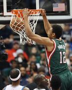 Milwaukee Bucks' Jabari Parker dunks as Minnesota Timberwolves' Corey Brewer, lower left, watches in the first quarter of an NBA basketball game, Wednesday, Nov. 26, 2014, in Minneapolis. AP Photo/Jim Mone)