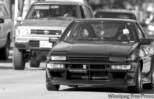 TREVOR.HAGAN@FREEPRESS.MB.CA Anh Ly Huynh drives her 1983 Toyota Trueno down Main Street. Purchasing cars from Japan with the steering on the right is a popular trend.