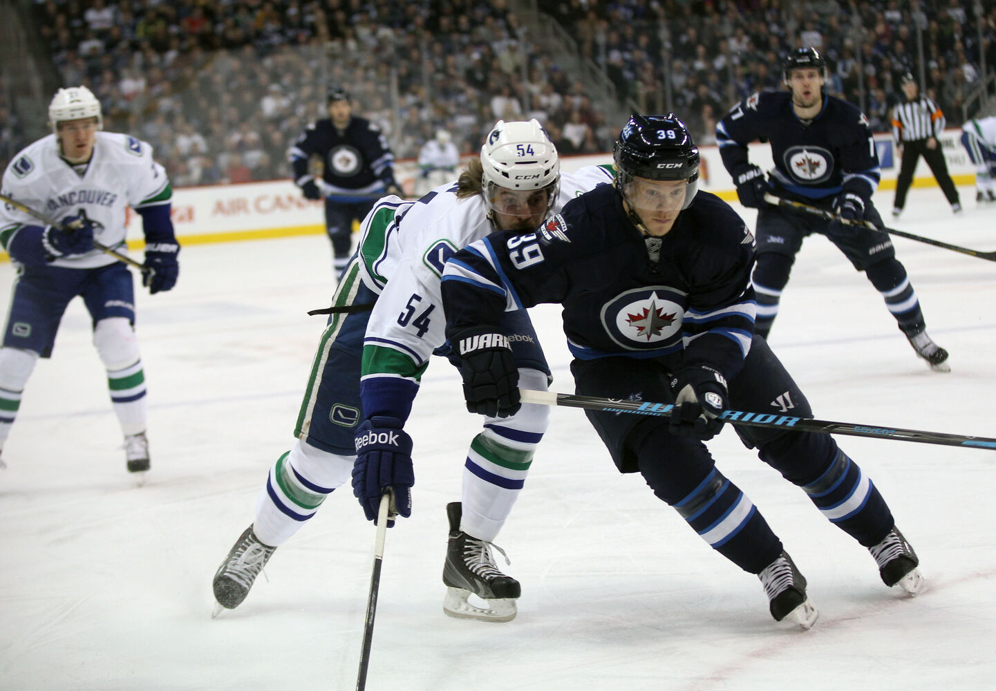 Winnipeg Jets' Tobias Endstrom and Vancouver Canucks' Kellan Lain run for the puck during the first period of Friday's game at Winnipeg's MTS Centre. (Joe Bryska / Winnipeg Free Press)