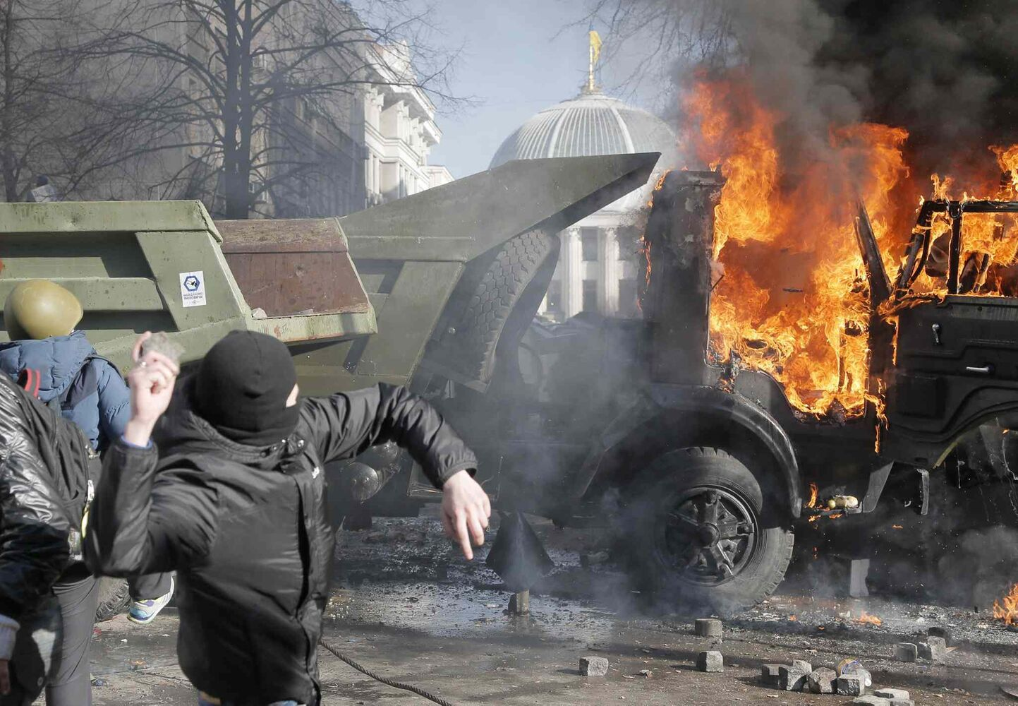 Anti-government protesters clash with riot police outside Ukraine's parliament in Kyiv as protests erupt in flames Tuesday. (Efrem Lukatsky / The Associated Press)