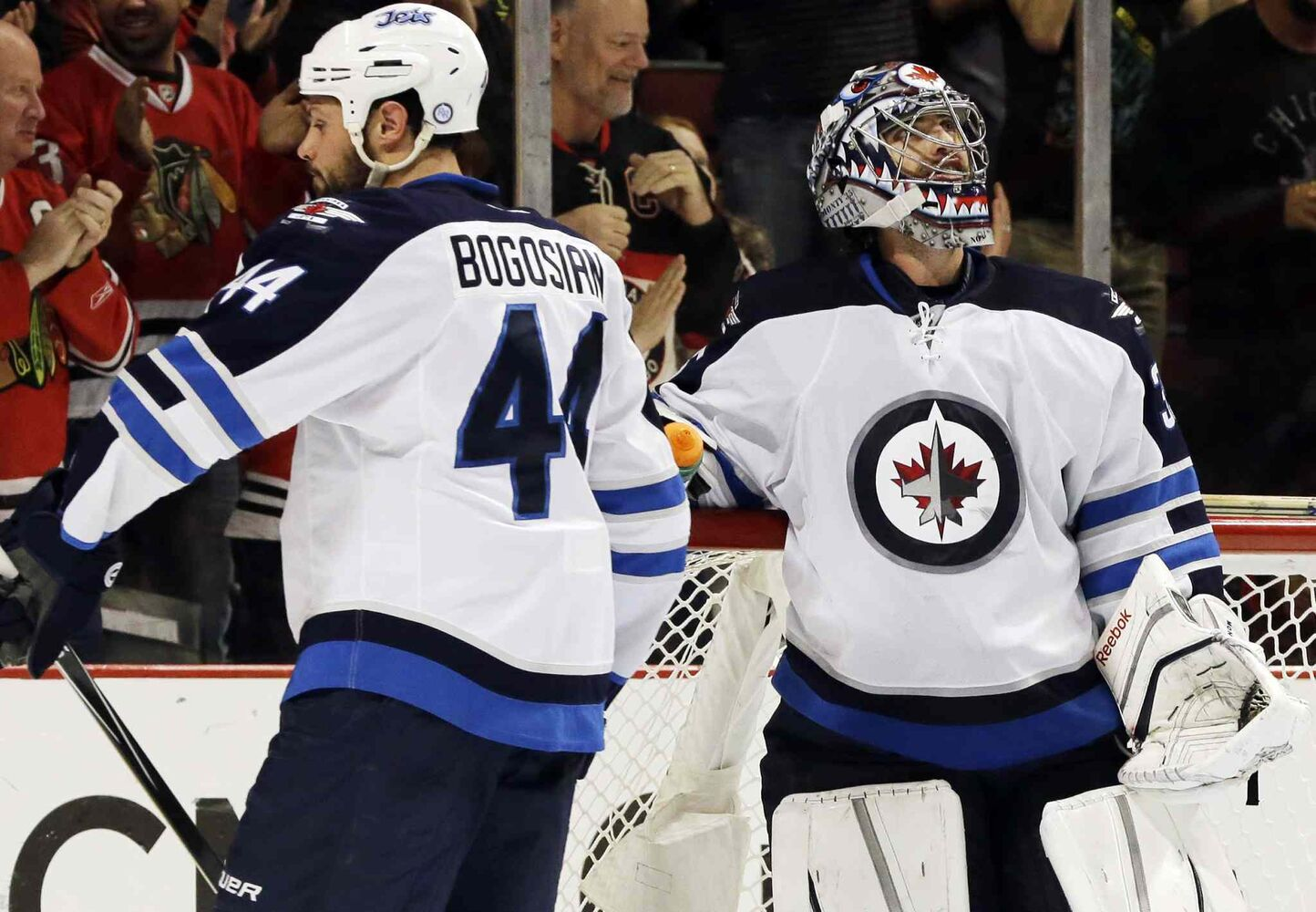Winnipeg Jets goalie Al Montoya (right) looks up at the scoreboard as Zach Bogosian (44) reacts after Chicago Blackhawks' Brandon Pirri scored during the second period.