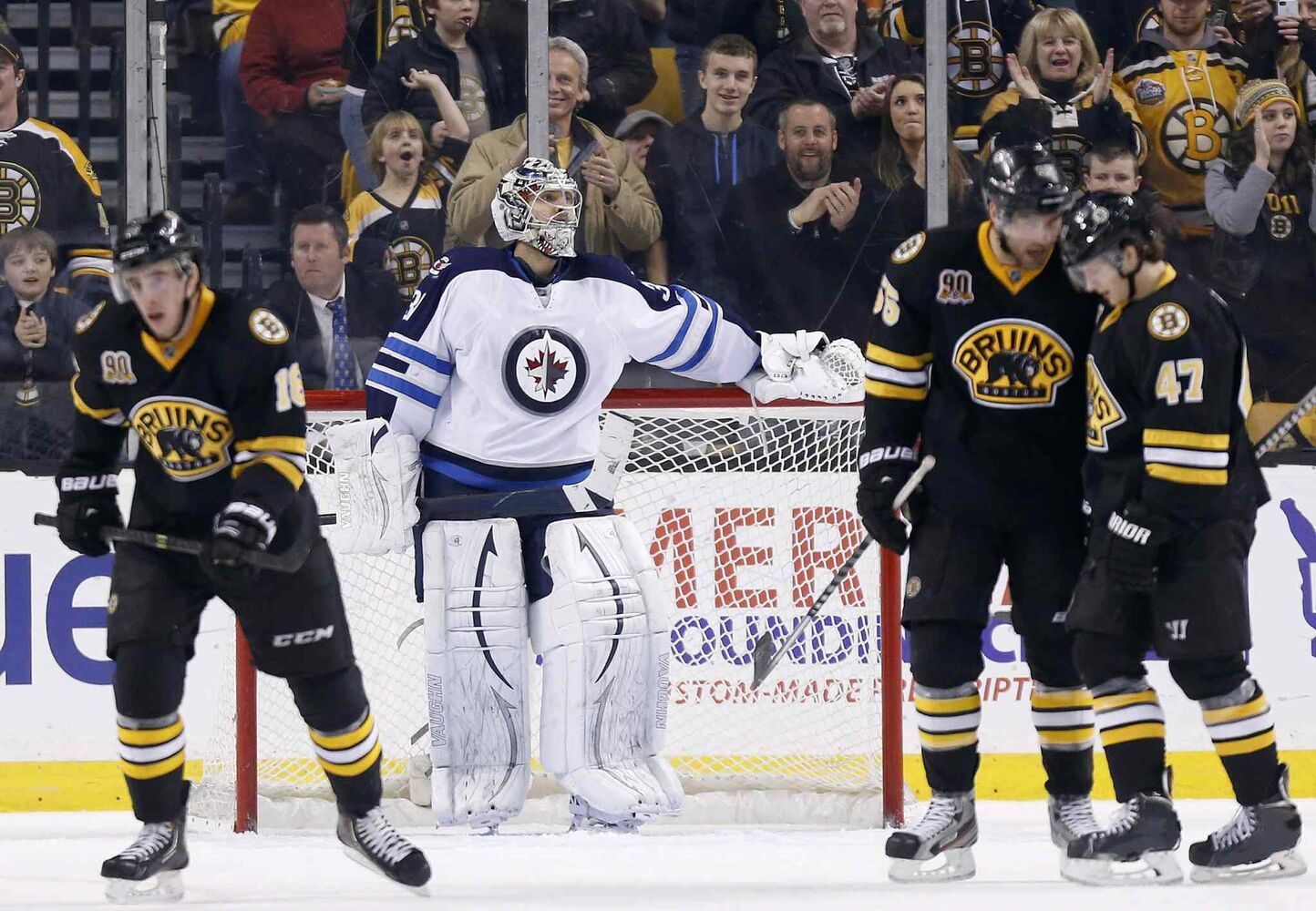 Winnipeg Jets' Ondrej Pavelec, centre, stands in the goal as Boston Bruins' Johnny Boychuk (55) and Torey Krug (47) celebrate a goal by teammate Reilly Smith, left, during third period in Boston Saturday.