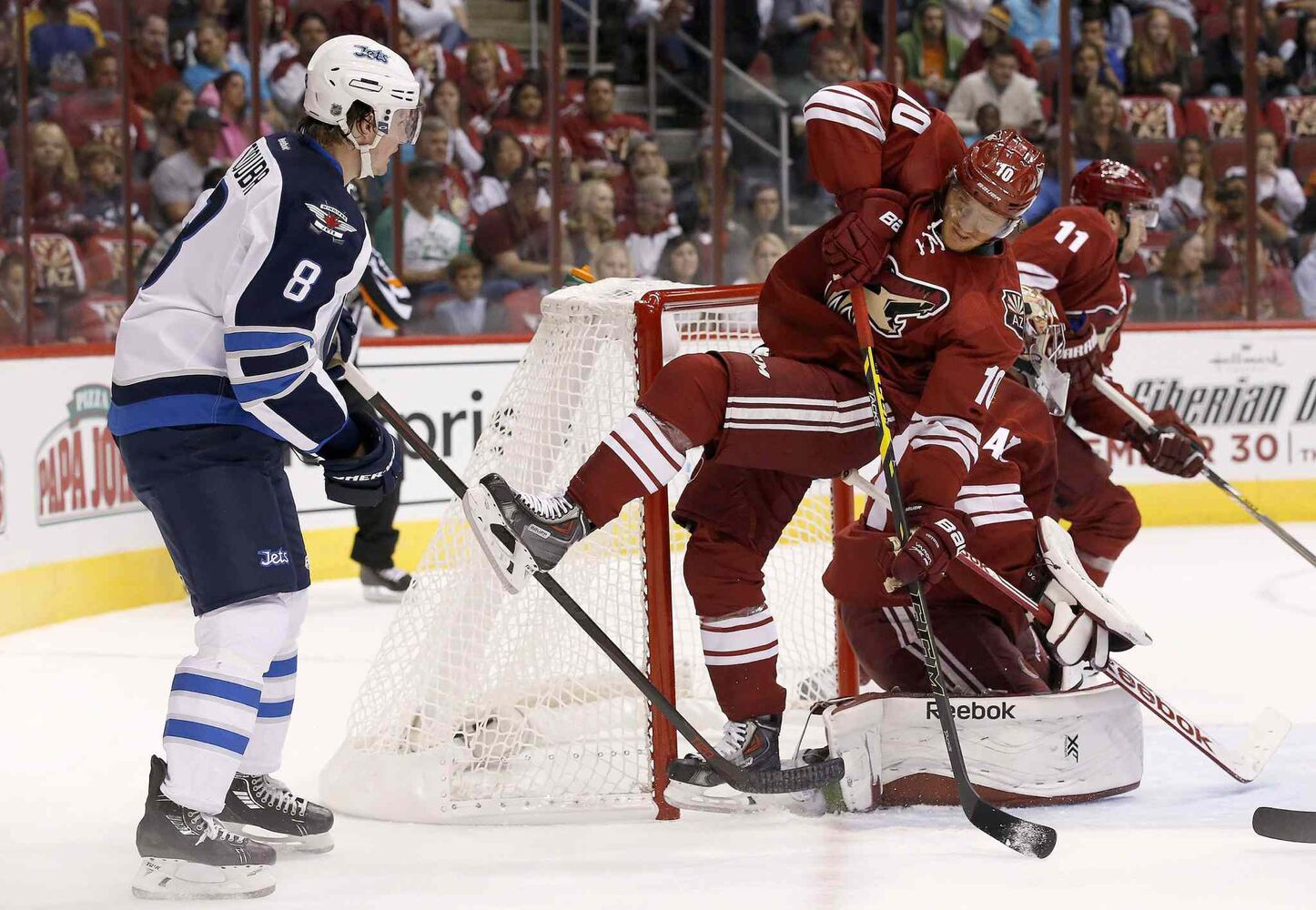 Arizona Coyotes' Martin Erat (10), of the Czech Republic, gets tripped up by Winnipeg Jets' Jacob Trouba (8) during the first period of an NHL hockey game Thursday. (Ross D. Franklin / The Associated Press)