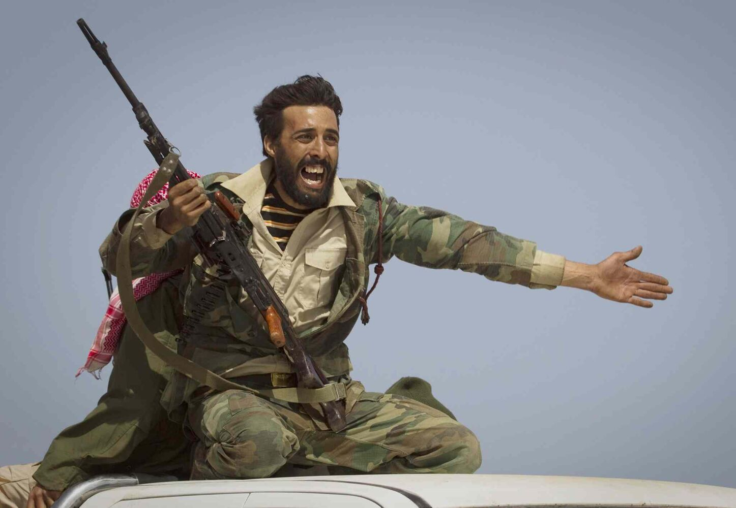 March 29, 2011: A Libyan rebel urges people to leave as shelling from Gadhafi's forces started landing on the frontline outside of Bin Jawaad, 150 kilometers (93 miles) east of Sirte, central Libya.