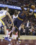 Cleveland Cavaliers' Tristan Thompson (13), from Canada, shoots over Golden State Warriors' David Lee (10) and Harrison Barnes (40) during the second quarter of an NBA basketball game Thursday, Feb. 26, 2015, in Cleveland. (AP Photo/Tony Dejak)