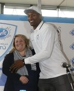 Former NBA All-Star Metta World Peace, right, hugs Anna Cremascoli, president of Pallacanestro Cantu' team, prior to a press conference in Milan, Italy, Thursday, March 26, 2015. Former NBA All-Star Metta World Peace has signed for Italian team Pallacanestro Cantu for the remainder of the season. World Peace, who changed his name from Ron Artest, was playing for the Sichuan Blue Whales in the Chinese Basketball Association after a long NBA career which included stints with the Chicago Bulls, Los Angeles Lakers and New York Knicks. (AP Photo/Luca Bruno)