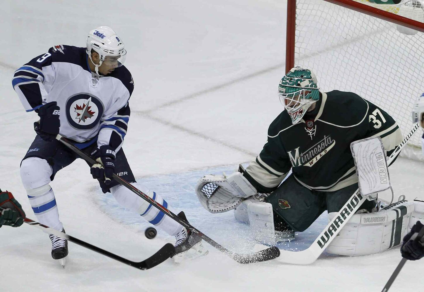 Minnesota Wild goalie Josh Harding (right) deflects a shot by Winnipeg Jets winger Evander Kane during the first period. (Ann Heisenfelt / The Associated Press)