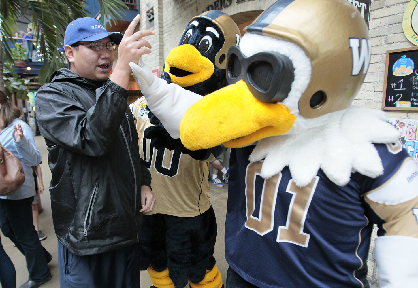 Mike Gladue high fives Buzz and Boomer at The Forks. (John Woods / Winnipeg Free Press)