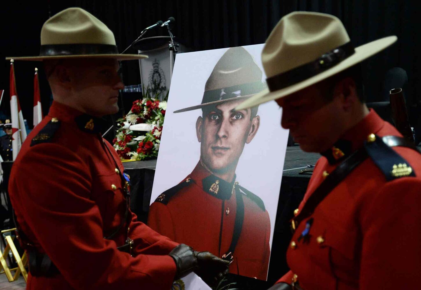 RCMP Officers flank a portrait of slain RCMP officer Const. Douglas Larche during the regimental funeral in Moncton Tuesday.