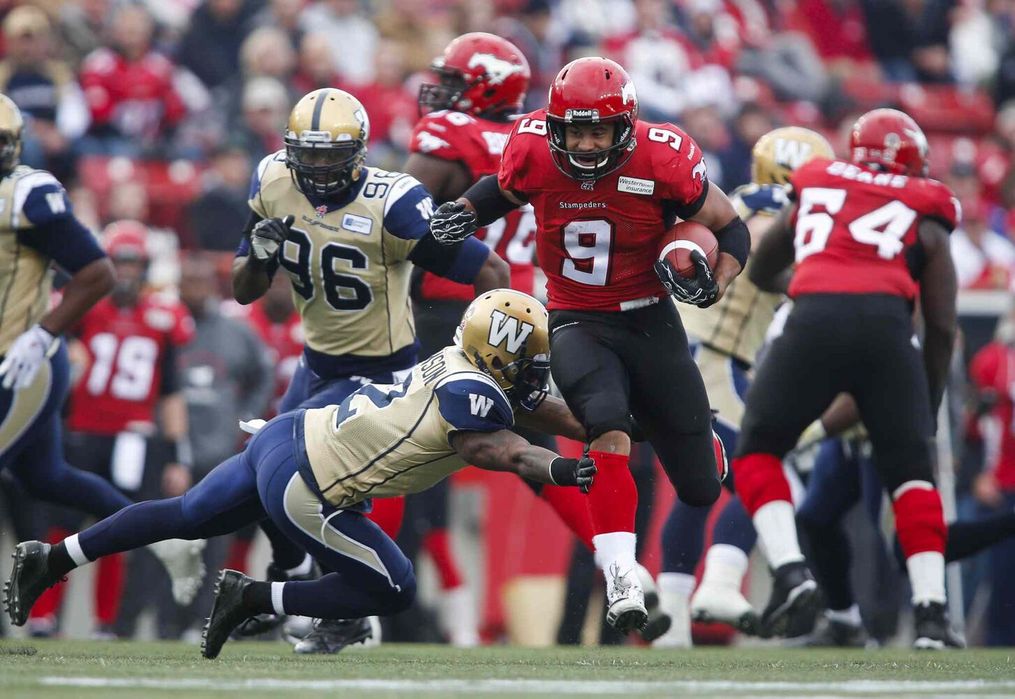Winnipeg Blue Bombers' Jovon Johnson (bottom) tries to stop Calgary Stampeders' Jon Cornish on his way to a touchdown during the first half. (Jeff McIntosh / The Canadian Press)