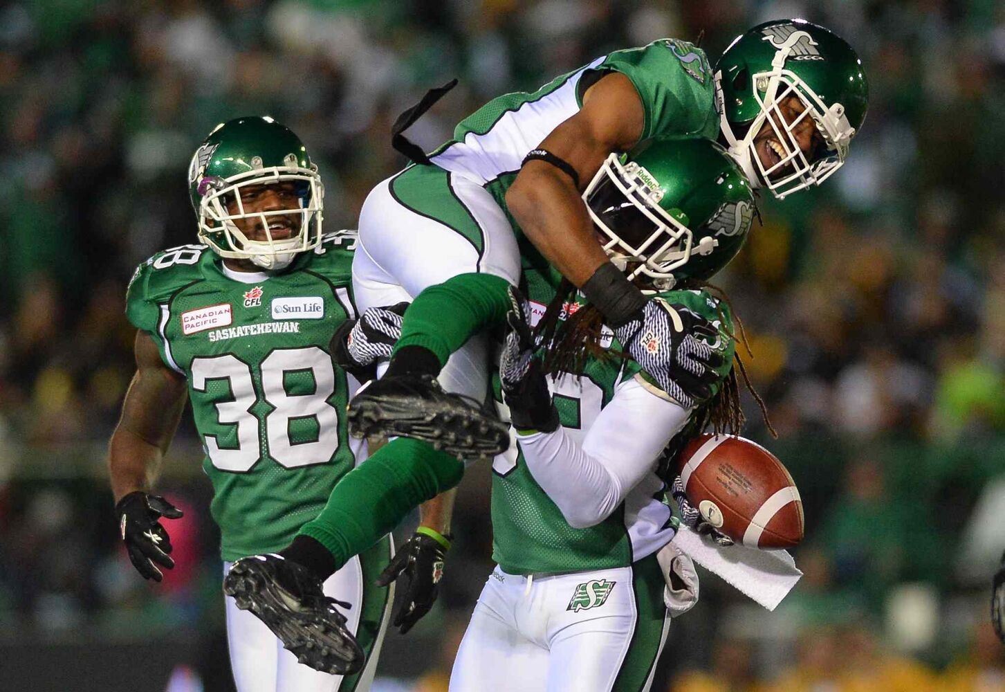 Saskatchewan Roughriders linebacker Weldon Brown (top) is hoisted by teammate defensive back Dwight Anderson following a pass interception against the Hamilton Tiger-Cats during the third quarter. (Liam Richards / The Canadian Press)