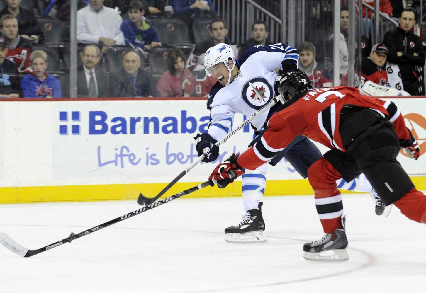 Winnipeg Jets forward Blake Wheeler takes a shot as New Jersey Devils' Mark Fayne attempts to get a stick on it during the first period.