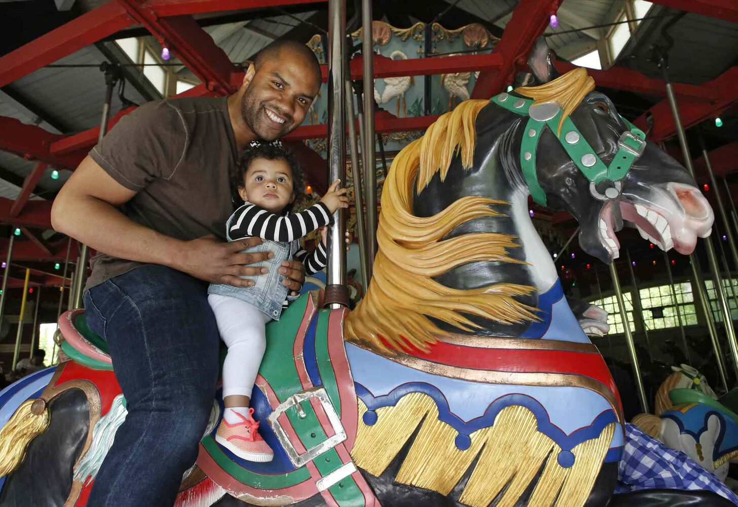 "Ron Sanon, 33, poses for a photo with 14-month-old Emmy at the Central Park carousel in New York. Fatherhood, Sanon said, is ""The greatest gift you can get in life. What my dad was to me, what my wife's dad was to her, you want to be that person they look up to. Like a superhero. Anything they're scared of, you can make it go away.""  (Kathy Willens / The Associated Press)"
