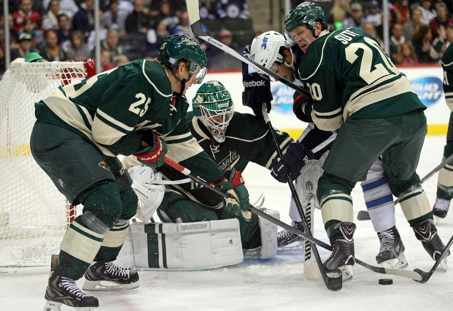 Minnesota Wild defencemen Jonas Brodin (left) and Ryan Suter (right) protect goaltender Josh Harding as Winnipeg Jets winger Eric Tangradi battles for the puck in the first period at the Xcel Energy Center Thursday night. The Jets lost 2-1. (JESSE JOHNSON / USA TODAY SPORTS / REUTERS)