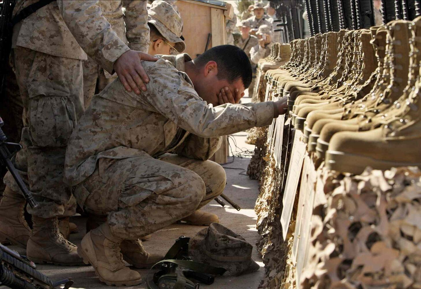 Feb. 2, 2005: A U.S. Marine cries during the memorial service for 31 killed U.S. servicemen at Camp Korean Village, near Rutbah, western Iraq.  (Anja Niedringhaus / The Associated Press)