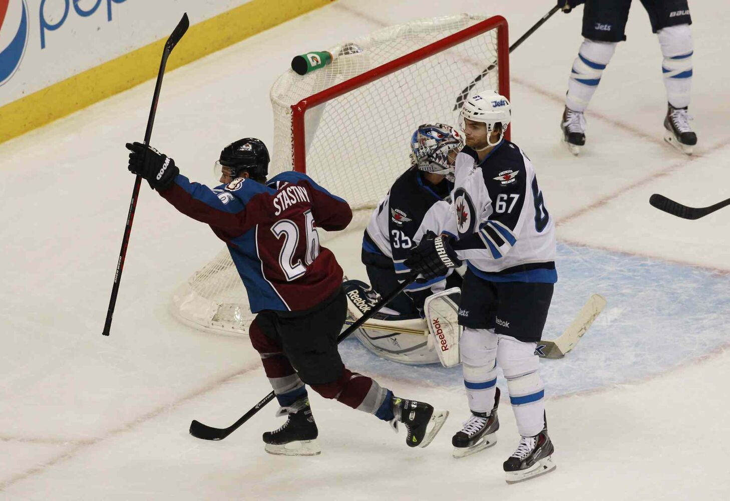 Colorado Avalanche center Paul Stastny (left) celebrates after scoring the scoring the game-winning goal as Al Montoya (centre) and winger Michael Froliklook on in the third period. (David Zalubowski / The Associated Press)