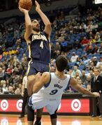 Minnesota Timberwolves' Ricky Rubio, right, of Spain, falls backward as he defends against Indiana Pacers' Luis Scola of Argentina as he shoots in the first quarter of a preseason NBA basketball game, Tuesday, Oct. 21, 2014, in Minneapolis. (AP Photo/Jim Mone)