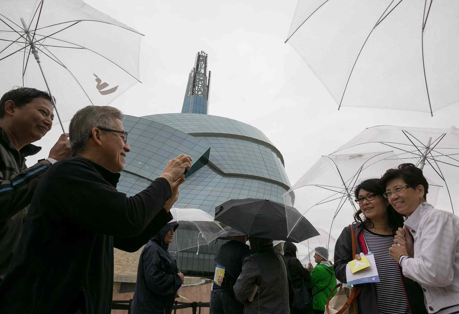 Frank Yong snaps a photo of his wife Teresa and her friend Jenny Lee, all from British Columbia, while they wait in the rain for their preview tour at the Canadian Museum for Human Rights on Saturday. The rain kept away some of the people with reserved tickets, allowing walk-ups to gain access to the guided tour of four of 11 galleries. The rest of galleries open Sept. 27. (Melissa Tait / Winnipeg Free Press)
