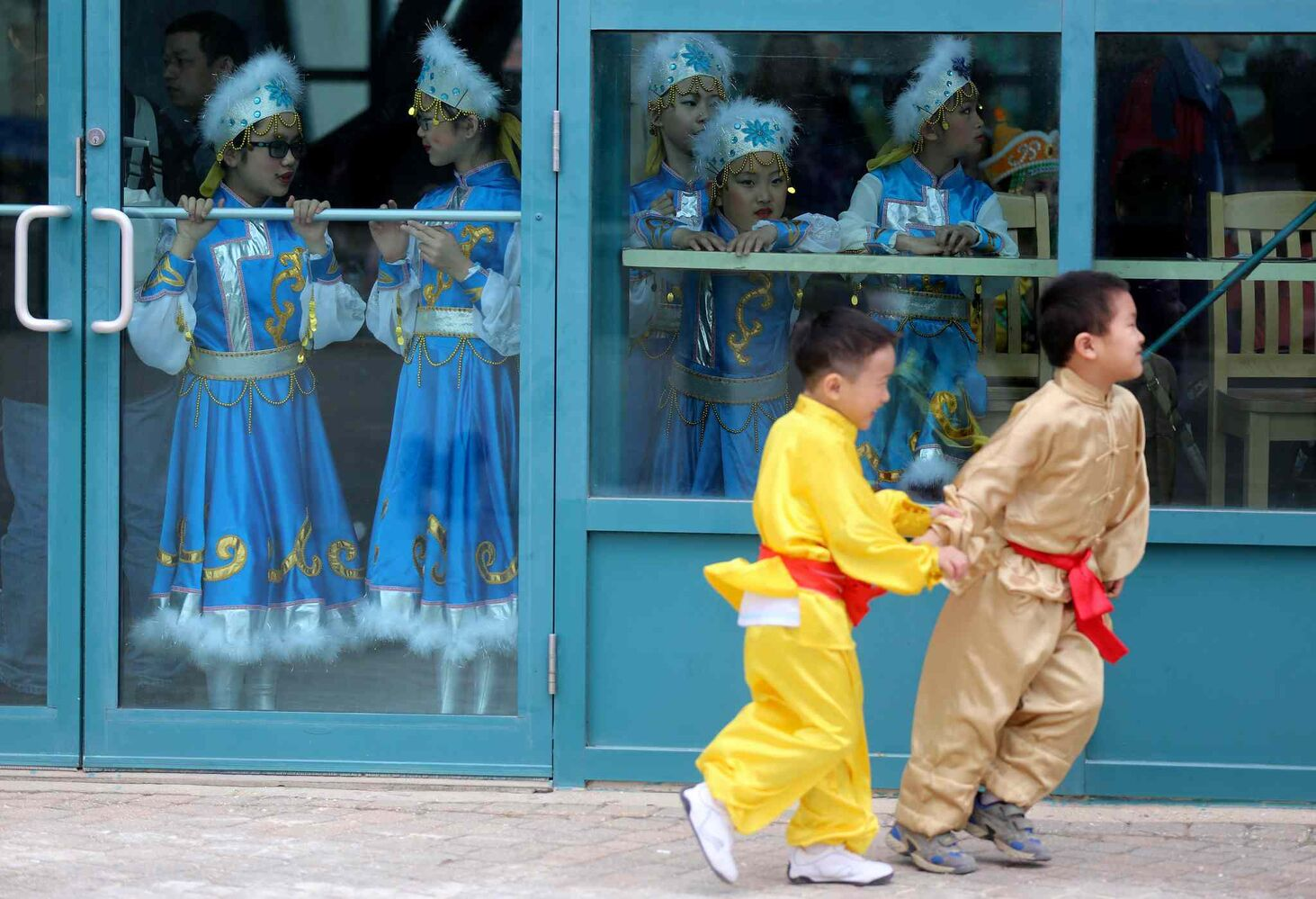 A young performer from the Great Wall Performing Arts school is pulled away by his friend after teasing another group of performers prior to taking the stage during Asian Heritage Month celebrations at The Forks, Sunday. (TREVOR HAGAN / WINNIPEG FREE PRESS)