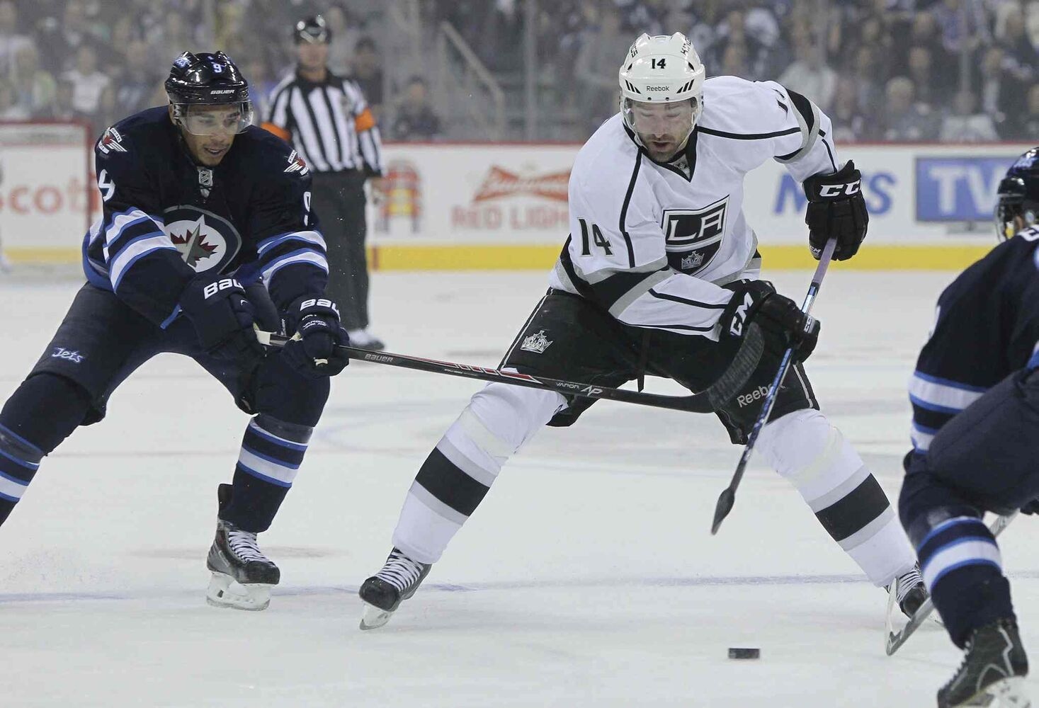 Winnipeg Jets' Evander Kane (9) tries to slow down Los Angeles Kings' Justin Williams (14) in the first period. (MIKE DEAL / WINNIPEG FREE PRESS)
