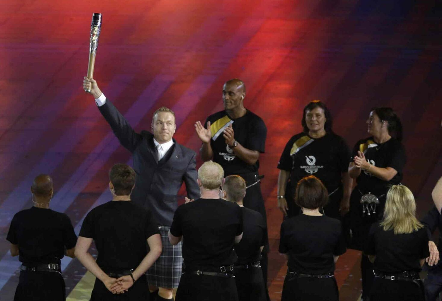 Sir Chris Hoy holds up the Queen's baton during the opening ceremony for the Commonwealth Games 2014. (Kirsty Wigglesworth / The Associated Press)