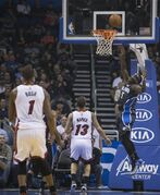 Orlando Magic's Victor Oladipo (5) lays up the ball after his steal against the Miami Heat's Shabazz Napier (13) and Chris Bosh (1) during the first half of an NBA basketball game in Orlando, Fla., Saturday, Nov. 22, 2014. (AP Photo/Willie J. Allen Jr.)