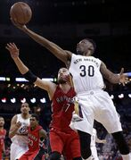 New Orleans Pelicans guard Norris Cole (30) goes to the basket in front of Toronto Raptors center Jonas Valanciunas (17) in the second half of an NBA basketball game in New Orleans, Monday, Feb. 23, 2015. The Pelicans won 100-97. (AP Photo/Gerald Herbert)