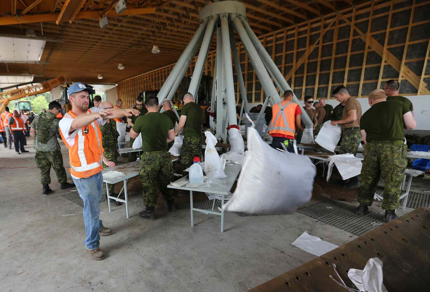 Soldiers from CFB Shilo and workers from the Municipality of Portage la Prairie work to make sandbags at the Portage Yard on Saturday.
