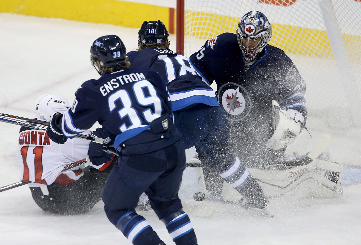 Stephen Gionta slides in front of the Winnipeg Jets net as Toby Enstrom, Bryan Little and goaltender Al Montoya all try to stop the puck during the first period. (Trevor Hagan / The Canadian Press)
