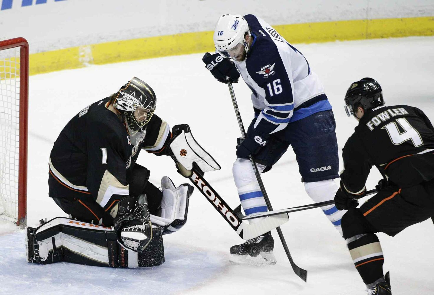 Winnipeg Jets' Andrew Ladd (16) tries to score against Anaheim Ducks' goalie Jonas Hiller, left, as the Ducks' Cam Fowler defends during first period in Anaheim Tuesday. (Jae C. Hong / The Associated Press)