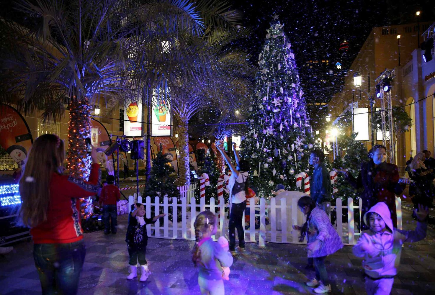 Visitors enjoy artificial snow spraying over a Christmas tree at the Jumeirah Beach Residence, JBR Walk in Dubai, United Arab Emirates, Wednesday, Dec. 25, 2013.  (The Associated Press)