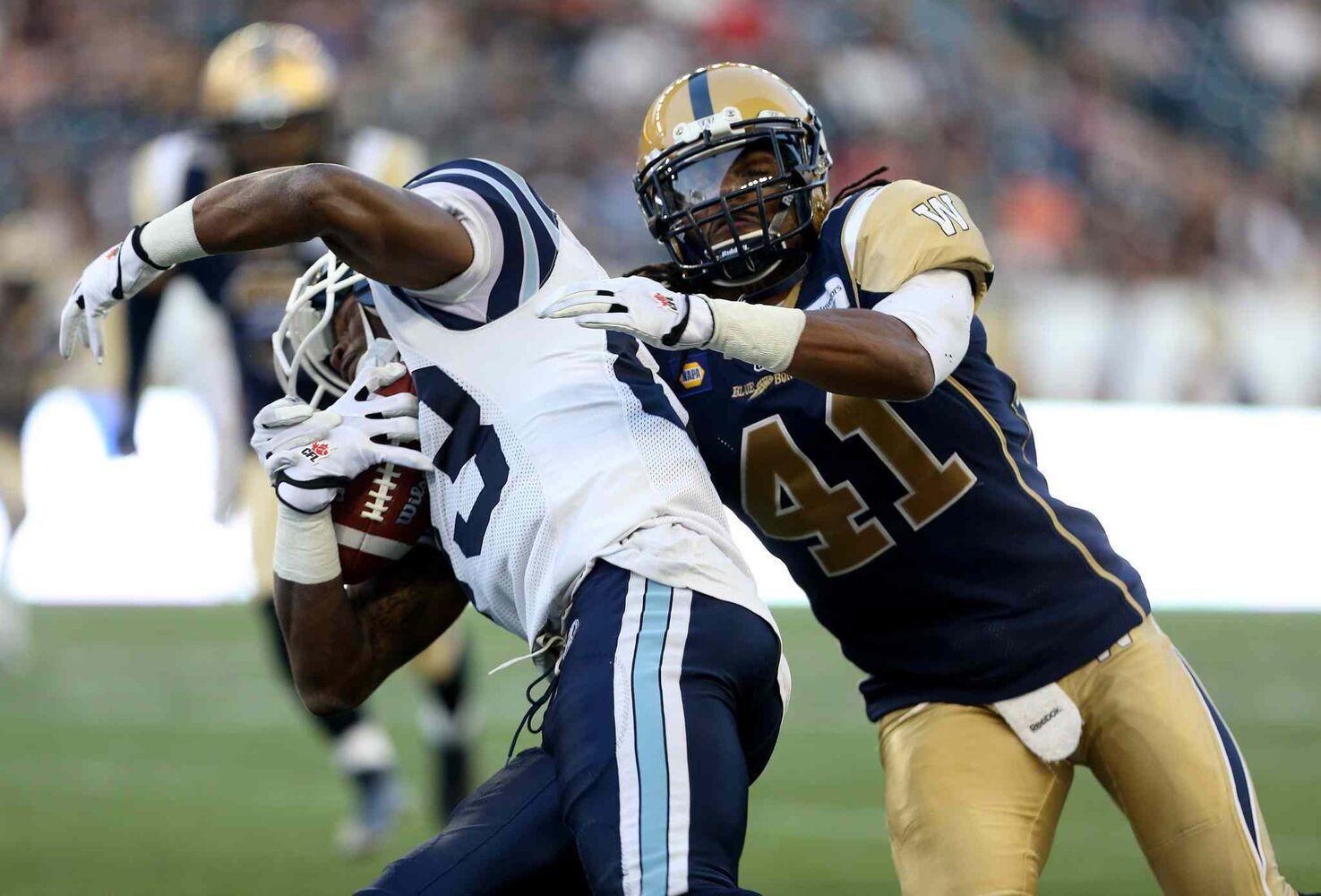 Toronto's Terrell Sinkfield spins off of Winnipeg's Don Unamba during the first half. (TREVOR HAGAN / THE CANADIAN PRESS)