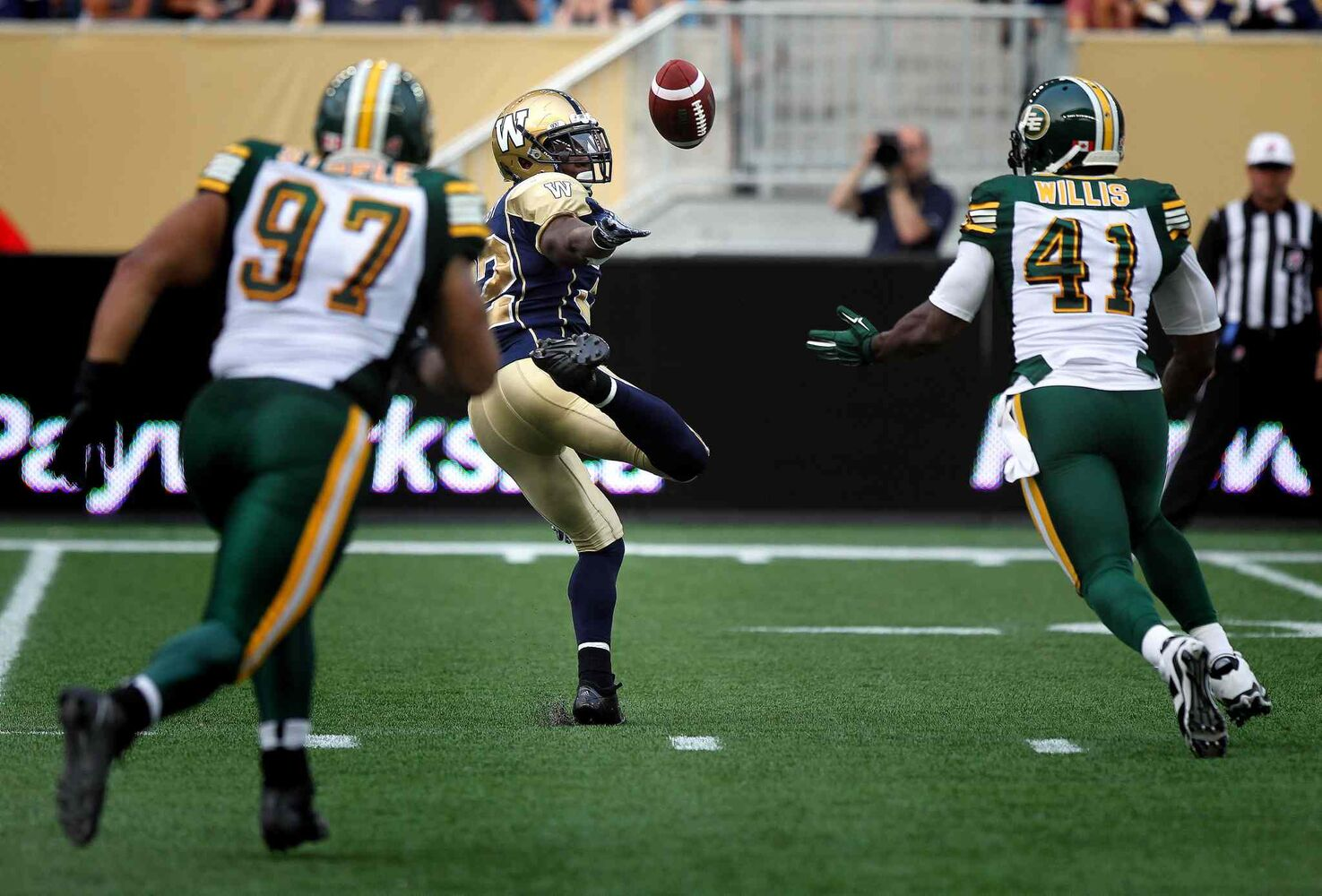 Winnipeg Blue Bombers' running back Nic Grigsby bobbles a pass into the waiting hands of Edmonton Eskimos' #41 Odell Willis early in the game Thursday. Willis took it and ran to score the Eskimo's opening touch down.   (Phil Hossack / Winnipeg Free Press)
