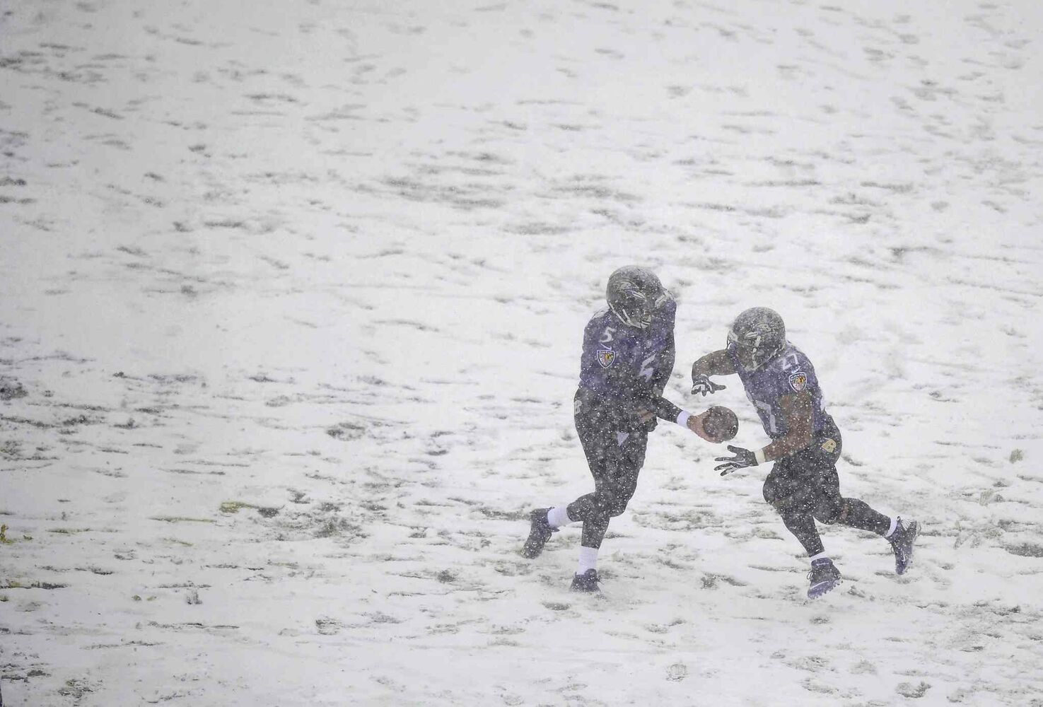 Baltimore Ravens quarterback Joe Flacco (left) hands the ball off to running back Ray Rice as snow falls in the first half of the game against the Minnesota Vikings.