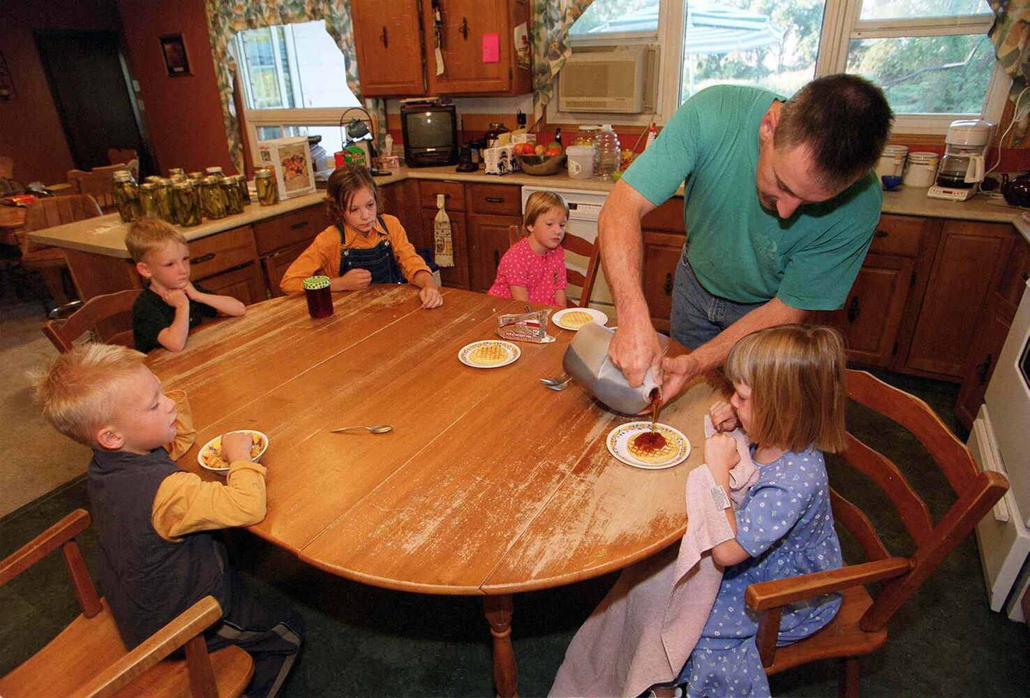 Ed Lavich pours syrup on his daughter Maryn's waffle on the morning of the children's first day of kindergarten. (JEFF DE BOOY / WINNIPEG FREE PRESS files)