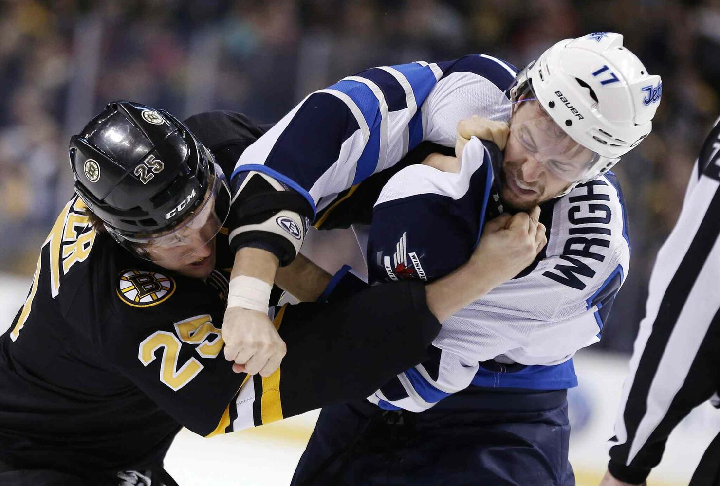Boston Bruins' Matt Fraser (25) and Winnipeg Jets' James Wright (17) fight in the first period of an NHL hockey game in Boston Saturday. (Michael Dwyer / The Associated Press)