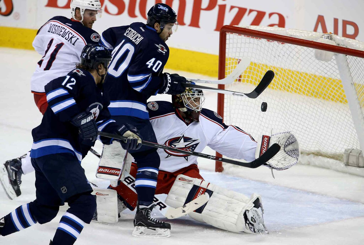 Columbus Blue Jackets' James Wisniewski (21) and Winnipeg Jets' Olli Jokinen (12) look on as Devin Setoguchi (40) tries to bat the puck past goaltender Curtis McElhinney (31) during the first period Saturday. McElhinney made the circus save.  (Trevor Hagan / Winnipeg Free Press)
