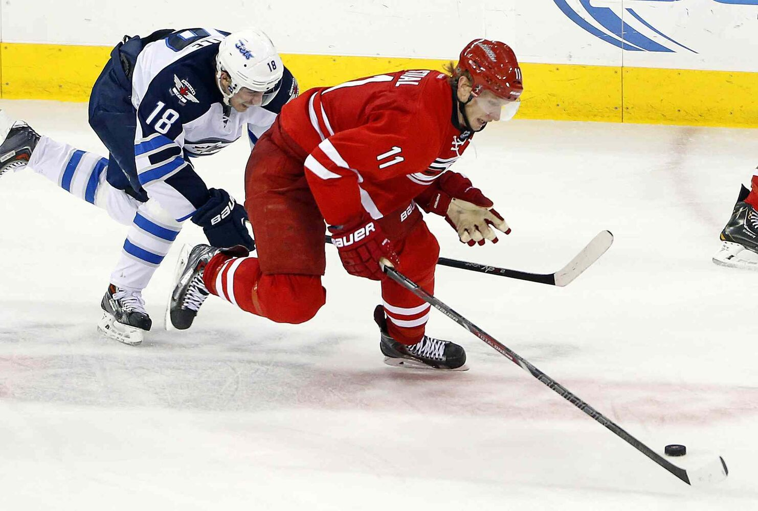 Carolina Hurricanes' Jordan Staal (11) tries to skate away from Winnipeg Jets' Bryan Little (18) during the third period of Tuesday's game.