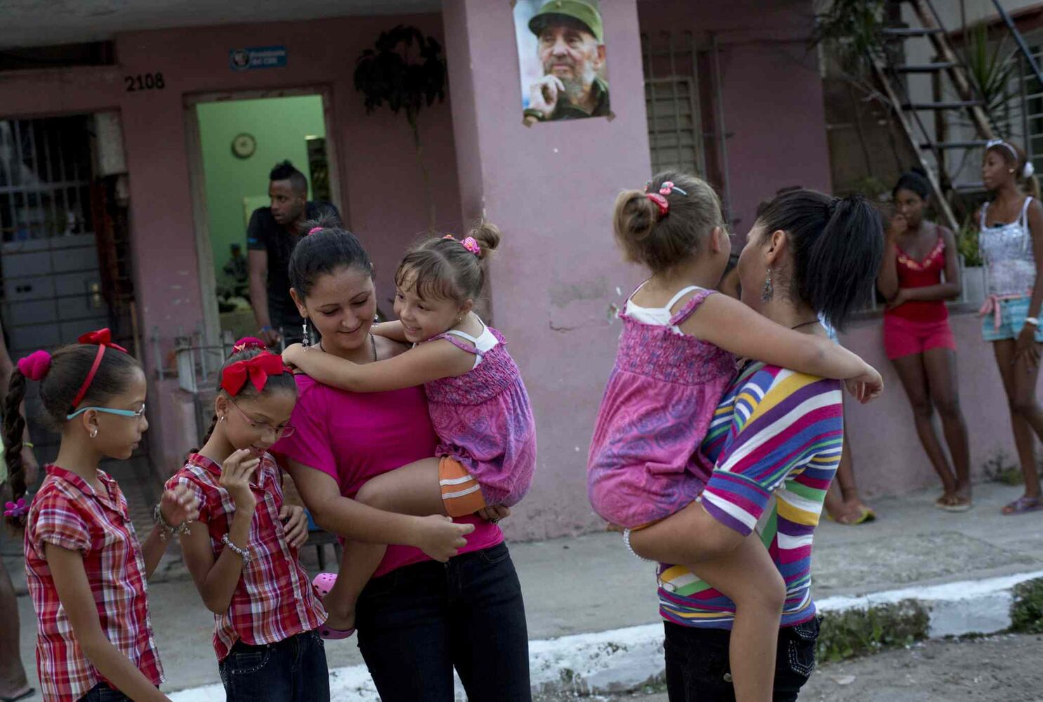 Nine-year-old twins Camila and Carla Rodriguez, (left), 18-year-old twins Kamar and Sahar Youssef and six-year-old twins Asley and Aslen Velazquez, pose for portraits along their street where a poster of Fidel Castro hangs in Havana, Cuba. (Ramon Espinosa / The Associated Press)