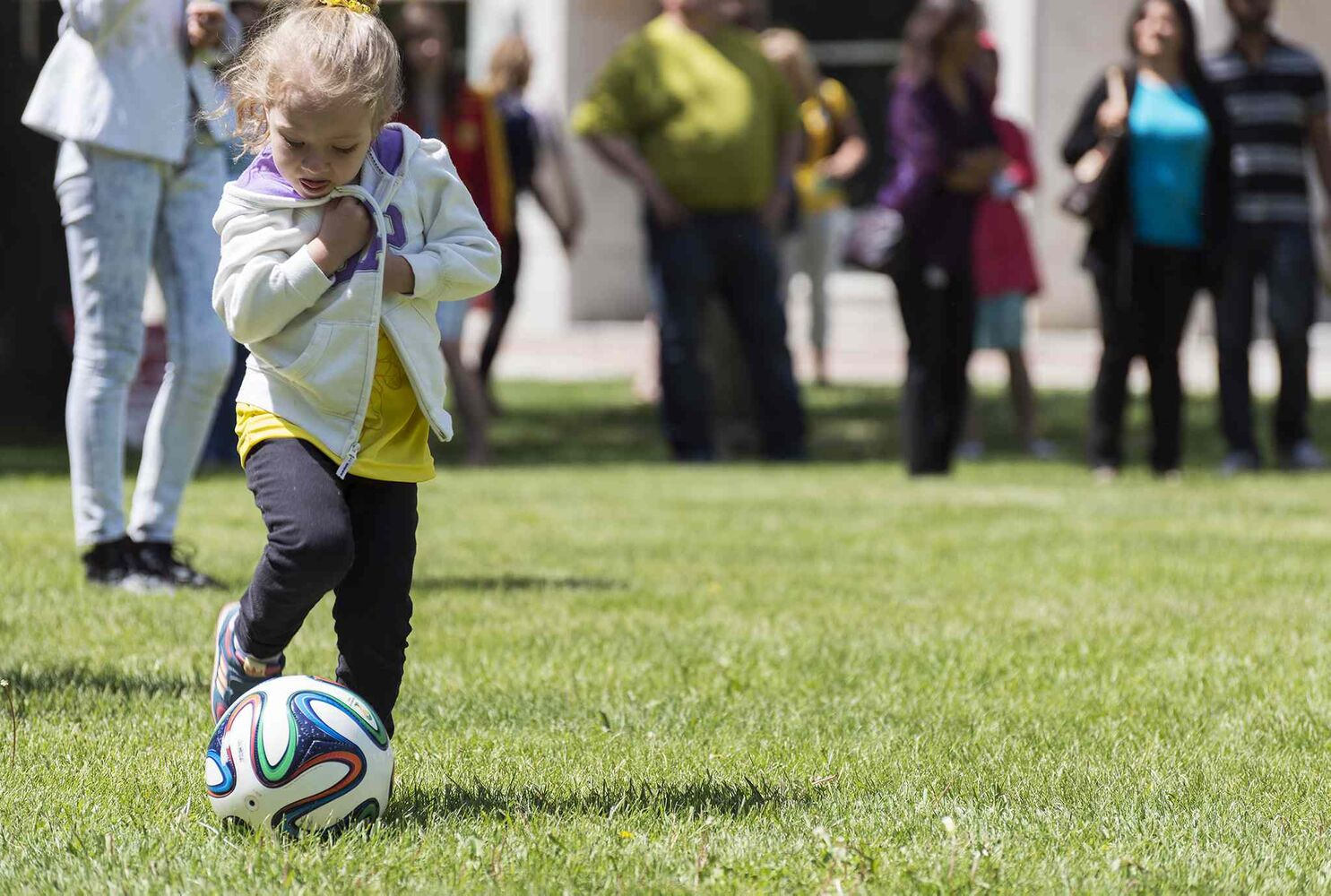 Annie Sophie Kneipp, 4, kicks the soccer ball at Stephen Juba Park for the World Cup pre game party. She and her family are visiting Winnipeg from Brazil. (Sarah Taylor / Winnipeg Free Press)