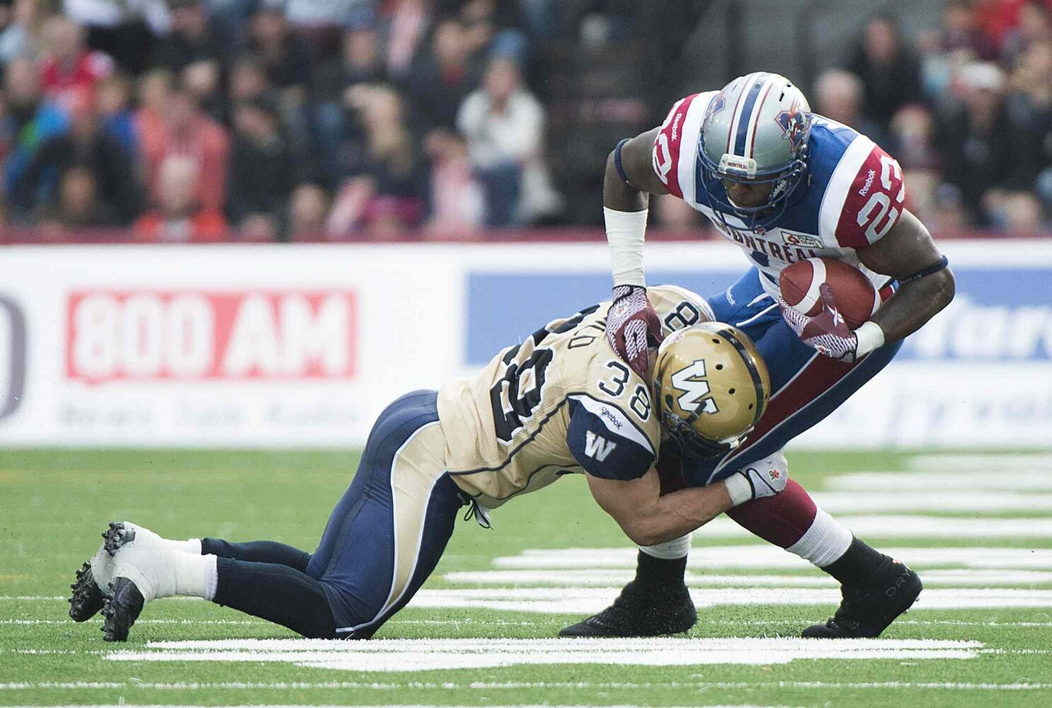Winnipeg Blue Bombers' Ian Wild, left, tackles Montreal Alouettes' Jerome Messam during second half CFL football action in Montreal Monday. (Graham Hughes / The Canadian Press)