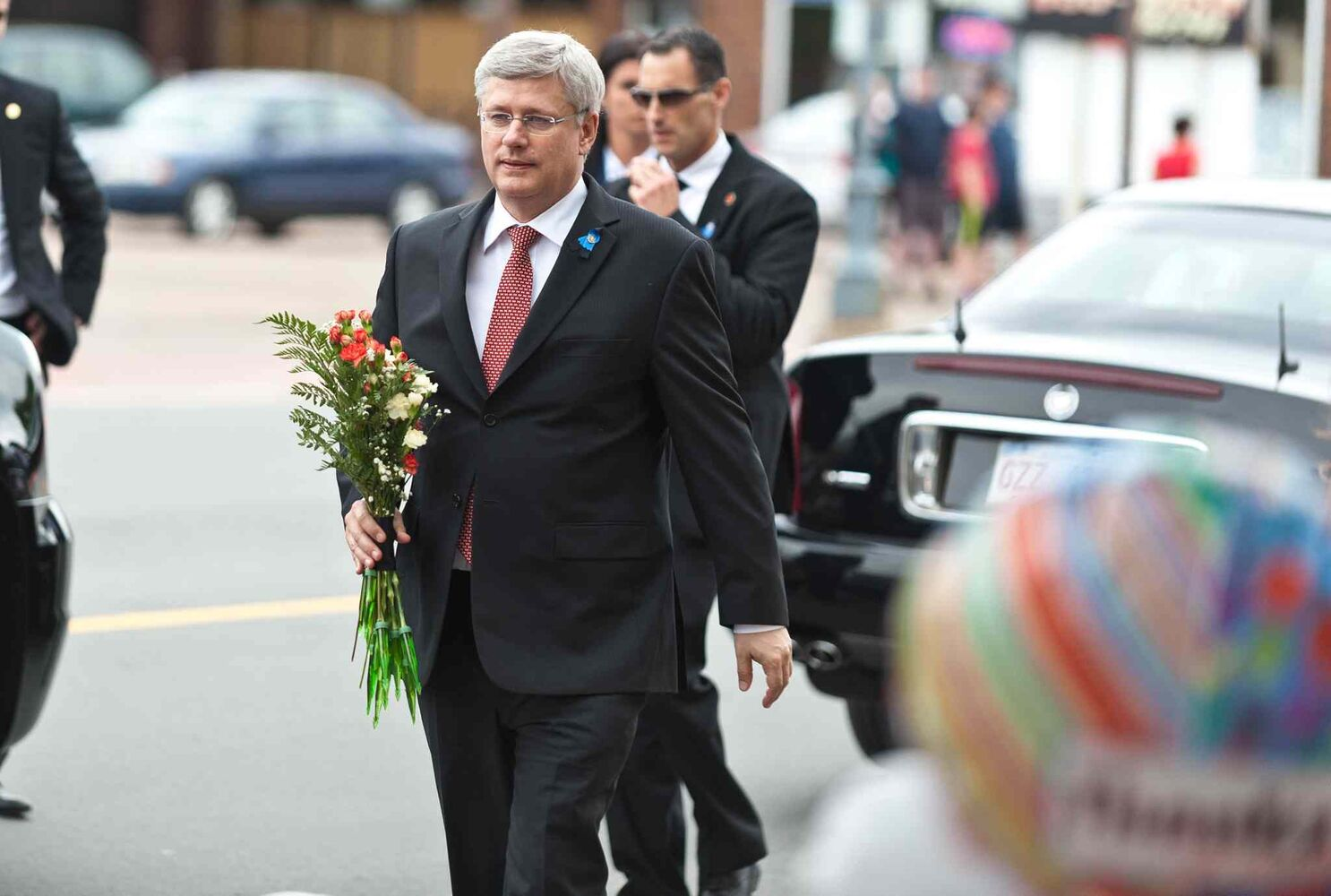 Prime Minister Steven Harper delivers flowers to the RCMP Headquarters in Moncton, N.B., following the regimental funeral for three slain RCMP officers.  (Marc Grandmaison / The Canadian Press)